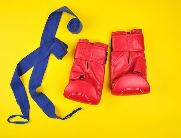 Par de luvas de boxe de couro vermelho e bandagem azul têxtil