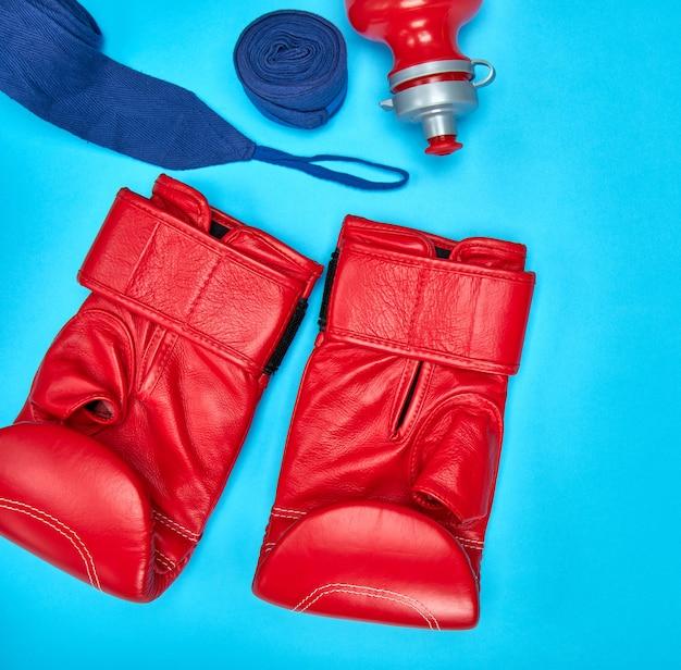 Par de luvas de boxe de couro vermelho e uma atadura de têxteis