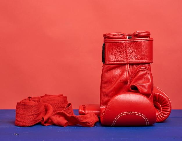 Par de luvas de boxe de couro vermelho sobre um fundo azul, equipamento desportivo