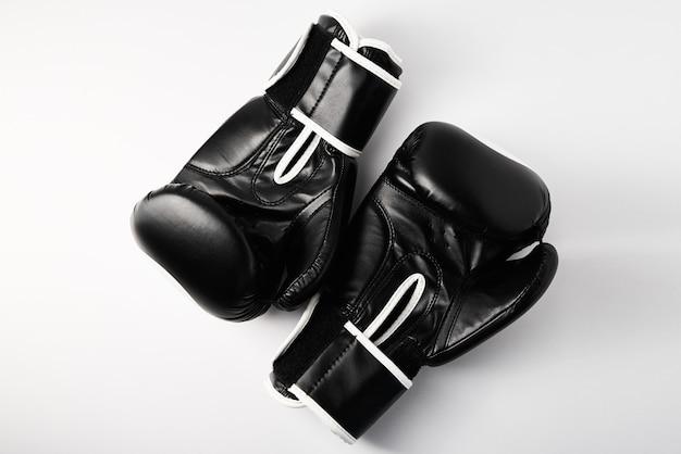 Par de luvas de boxe pretas na parede branca, close-up