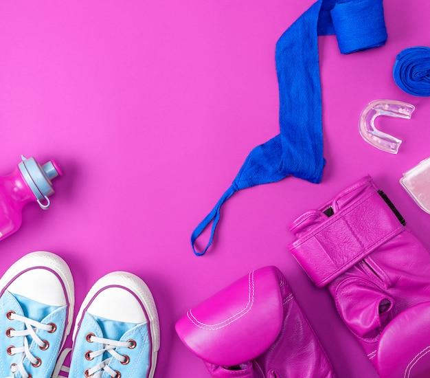 Par de luvas de boxe rosa de couro, uma bandagem têxtil azul e uma garrafa de água