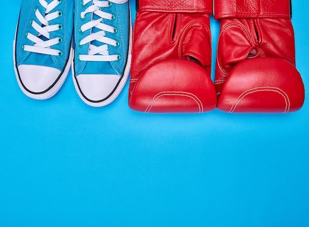 Par de luvas de boxe vermelhas e tênis azul têxtil
