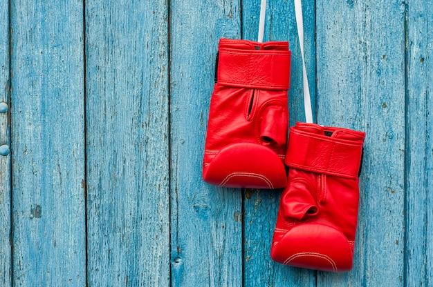 Par de luvas de boxe vermelhas penduradas em um prego