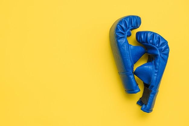 Par de luvas de treinamento de boxe azul sobre fundo amarelo. esportes, treinamento, artes marciais, tema de fitness
