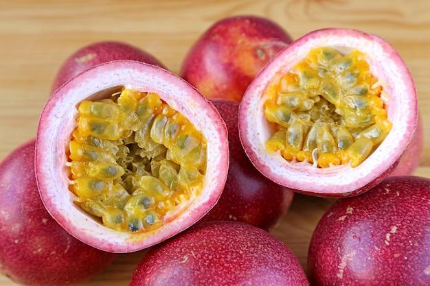 Par de maracujá maduro fresco cortado pela metade isolado na pilha de frutas inteiras