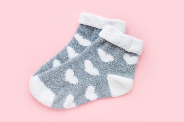 Par de meias femininas de inverno quente com estampa em forma de coração isolada sobre fundo rosa. presente de dia dos namorados