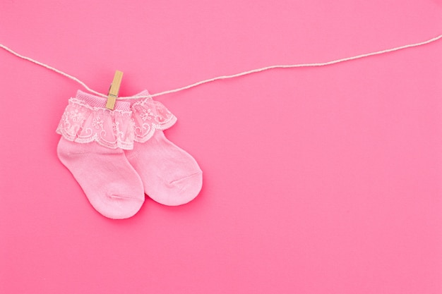 Par de meias rosa bebê fofo pendurado no varal no fundo rosa. acessórios para bebês. postura plana.