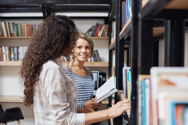 Par de meninas lindas em roupas elegantes casuais em pé perto de estantes de livros na biblioteca, olhando um ao outro, falando sobre a vida universitária tentando encontrar literatura para a lição de amanhã.