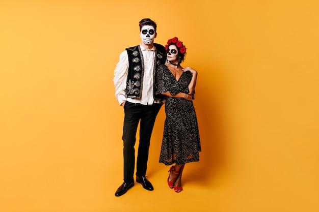 Par de namorados posa com rostos pintados no tradicional estilo mexicano. retrato de corpo inteiro de menina em vestido midi e cara com colete tradicional.