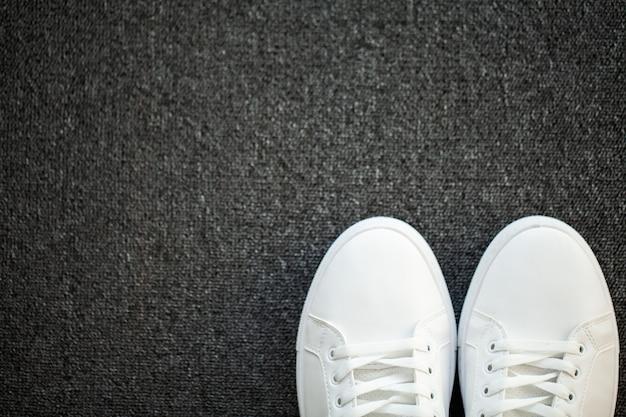 Par de novos tênis brancos elegantes no chão em casa