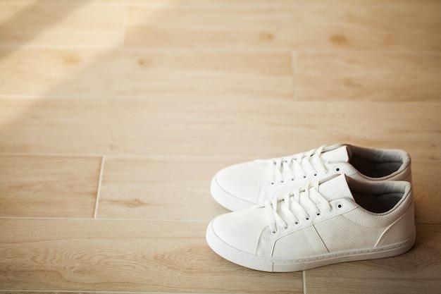 Par de novos tênis brancos elegantes no piso de madeira.