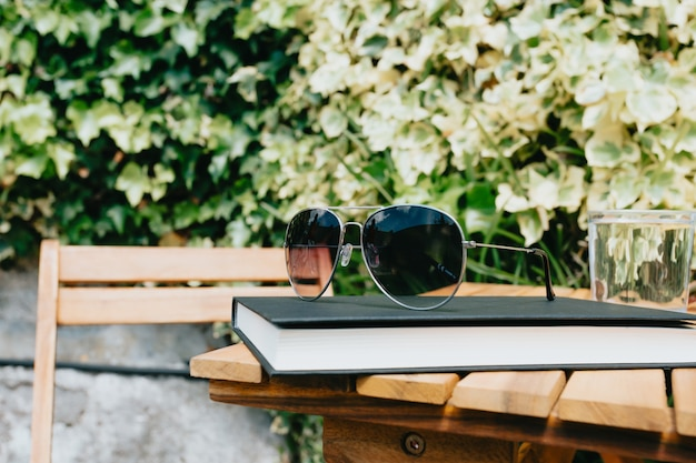 Par de óculos de sol sobre um livro e uma mesa de madeira, conceito de verão e férias