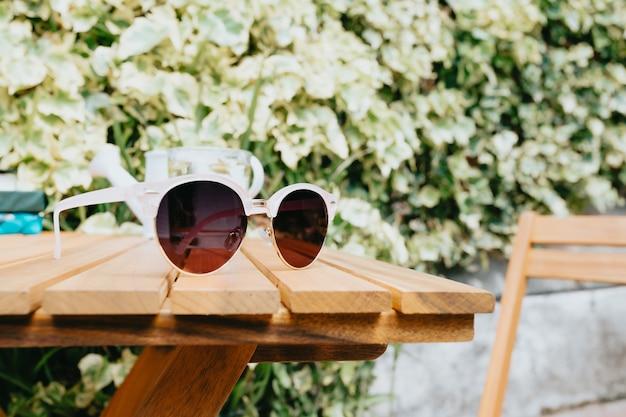 Par de óculos de sol sobre uma mesa de madeira, conceito de verão e férias
