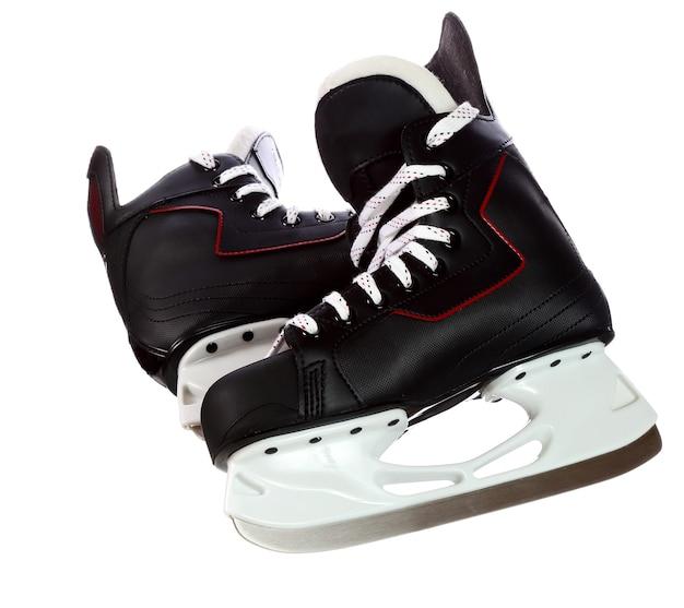Par de patins pretos de hóquei isolados no fundo branco