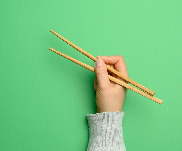 Par de pauzinhos de madeira em uma mão feminina em um fundo verde, close-up