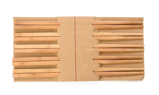 Par de pauzinhos de madeira isolados no fundo branco, os objetos são embrulhados em papel, conjunto