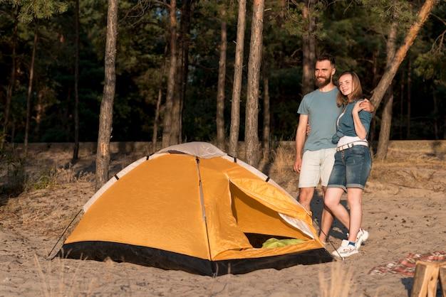 Par de pé por uma tenda a desviar o olhar