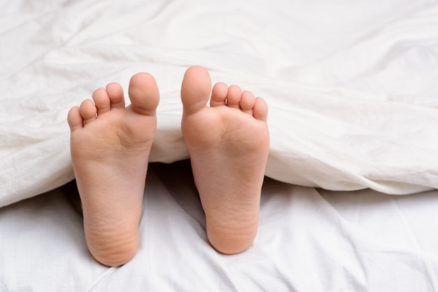 Par de pés da menina em uma cama