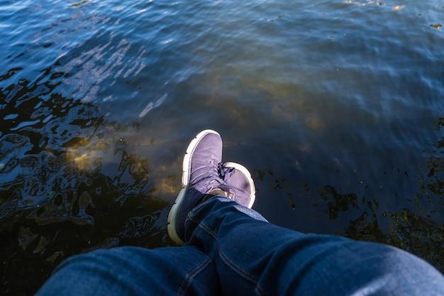 Par de pés relaxando à beira de um lago em uma doca de madeira. p