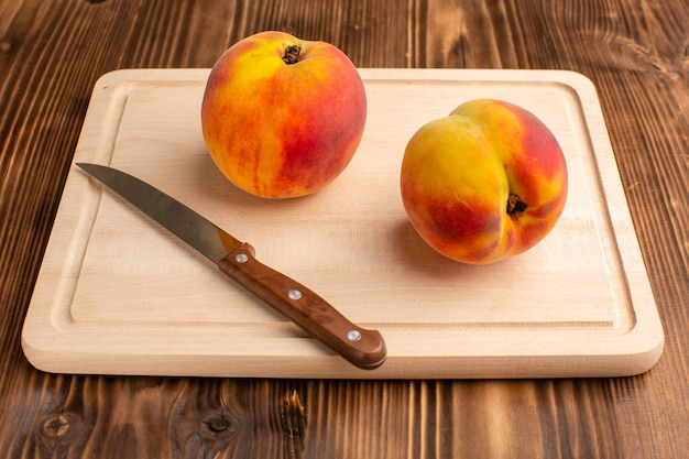 Par de pêssegos doces e maduros na madeira