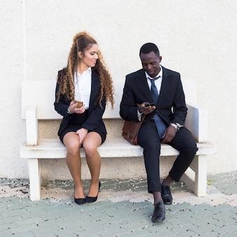 Par, de, pessoas negócio, olhar, smartphone, ligado, banco
