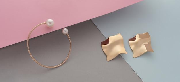 Par de pulseira dourada moderna e brincos ondulados em fundo de cor pastel