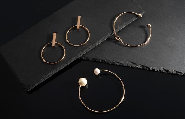 Par de pulseiras de ouro com pérolas e brincos em placas de pedra preta com espaço de cópia