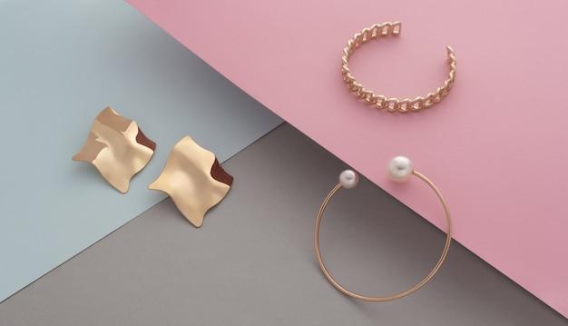 Par de pulseiras de ouro de design moderno e brincos de formato ondulado em fundo de cores pastel