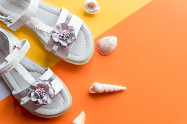 Par de sandálias de bebê brancas na cor de fundo vista de cima. sandálias femininas de couro estiloso e conchas do mar