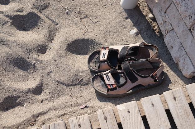 Par de sandálias na areia. calçado de verão para homem. verão quente nos trópicos. explorar e vagar pelo conceito.