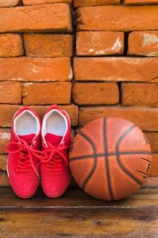 Par de sapatas do esporte e basquete na mesa de madeira contra a pilha de parede de tijolo
