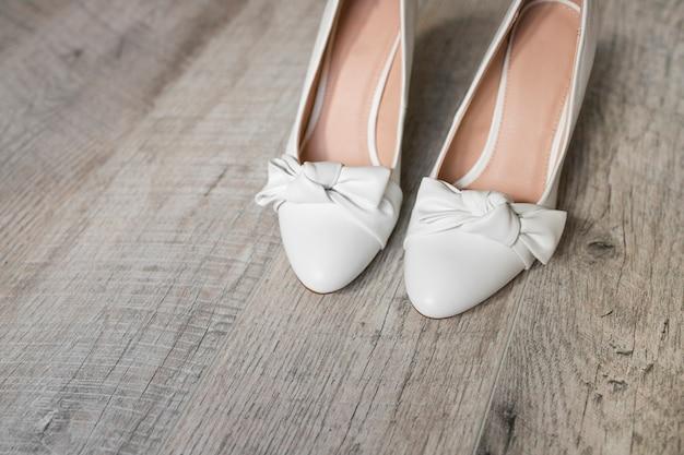 Par de sapatos brancos com laço em plano de fundo texturizado de madeira