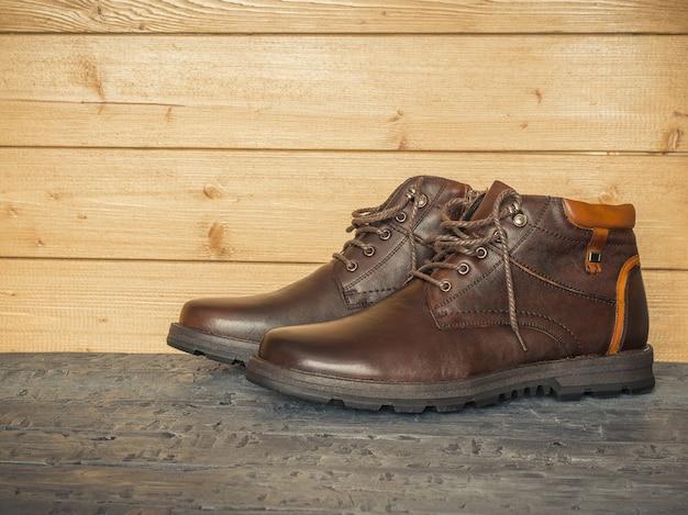 Par de sapatos clássicos masculinos marrons nas paredes de madeira do piso escuro. o conceito de sapatos masculinos casuais.