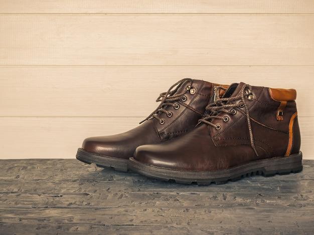 Par de sapatos clássicos masculinos marrons nas paredes de madeira do piso escuro. sapatos masculinos brutais.