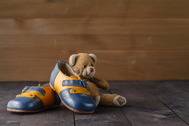 Par de sapatos de bebê na mesa de madeira