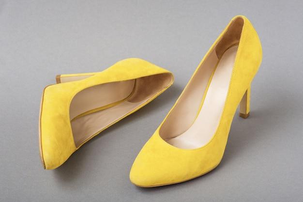 Par de sapatos de camurça amarela na moda em fundo cinza