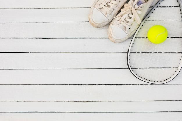Par de sapatos de desporto branco e raquete com bola de tênis na mesa de madeira