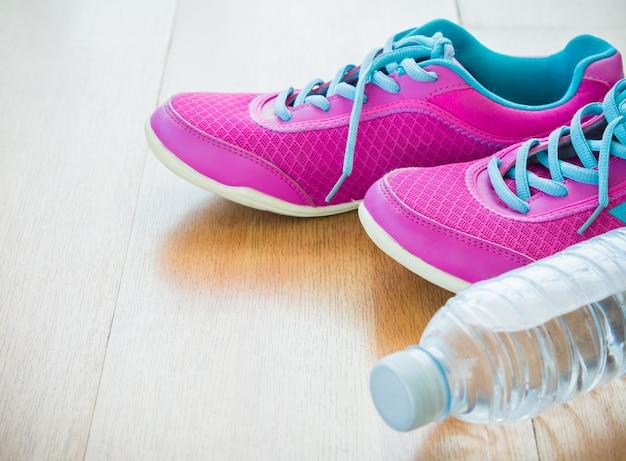 Par de sapatos de desporto-de-rosa e garrafa de água com fundo de madeira