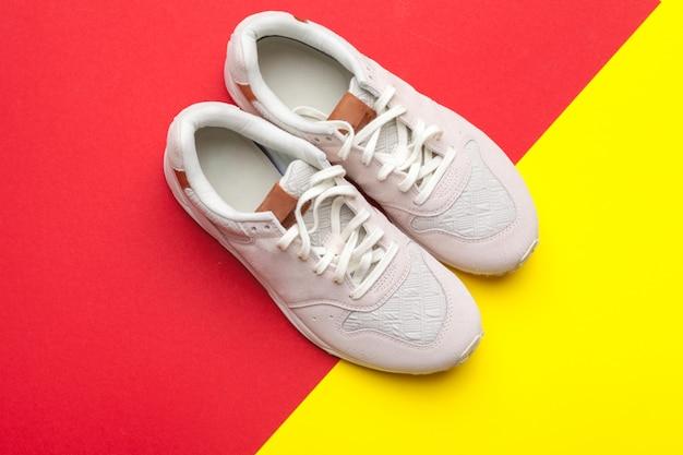 Par de sapatos de desporto em fundo colorido
