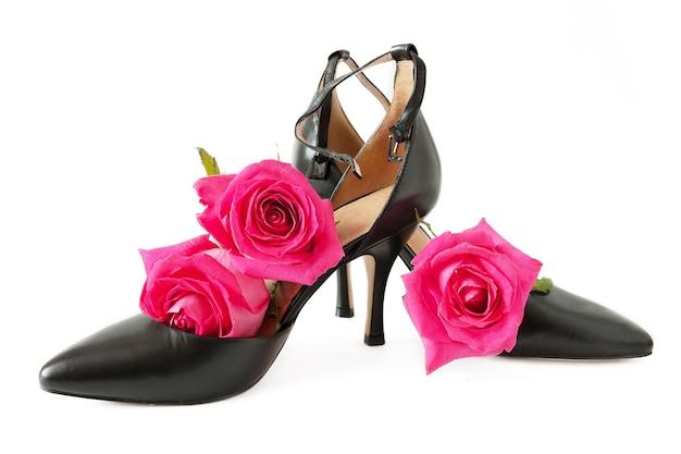 Par de sapatos de mulher negra e rosas frescas