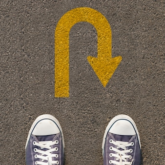 Par de sapatos em pé em uma estrada com sinal de trânsito