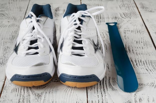 Par de sapatos esporte branco na parede de madeira, par de tênis branco sobre um piso de madeira