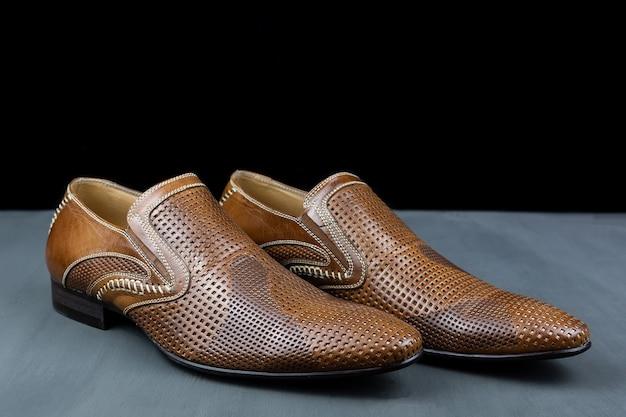 Par de sapatos marrons em um fundo preto. sapatos da moda masculina. sapatos masculinos clássicos em couro genuíno. acessórios masculinos. sapatos elegantes e estilosos