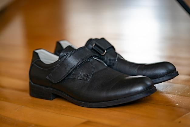 Par de sapatos pretos confortáveis, isolados em um piso de madeira.
