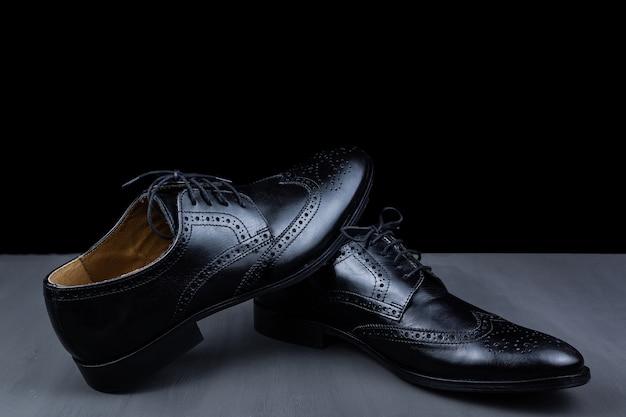 Par de sapatos pretos em um fundo preto. sapatos da moda masculina. sapatos masculinos clássicos em couro genuíno. acessórios masculinos. sapatos elegantes e estilosos