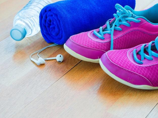 Par de sapatos rosa sport, toalha, garrafa de água no chão de madeira.