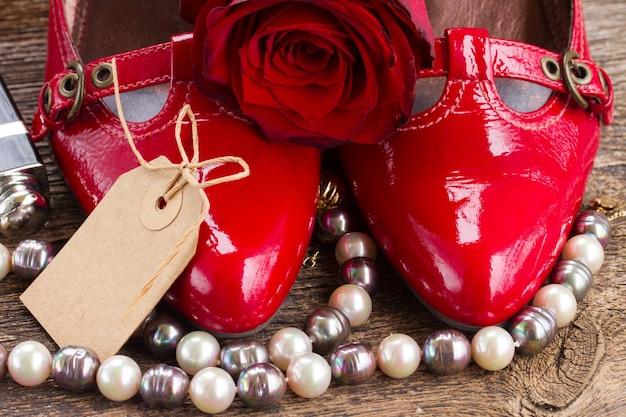 Par de sapatos vermelhos com flor rosa e etiqueta vazia