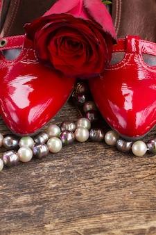 Par de sapatos vermelhos com flor rosa e joias de pérolas em madeira