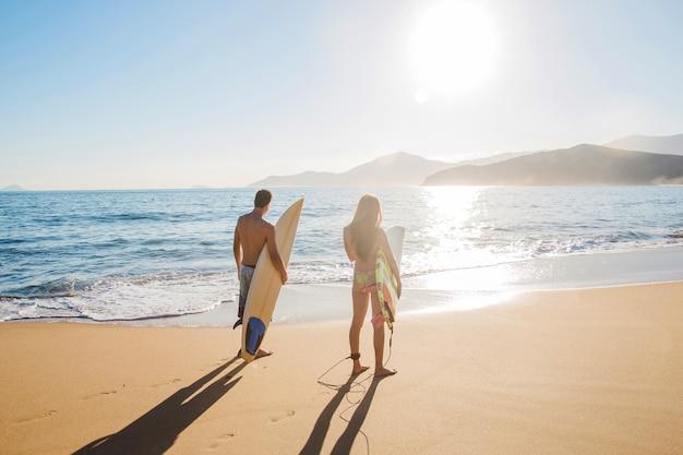 Par de surfistas na praia ensolarada