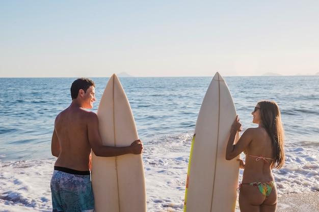 Par de surfistas na praia